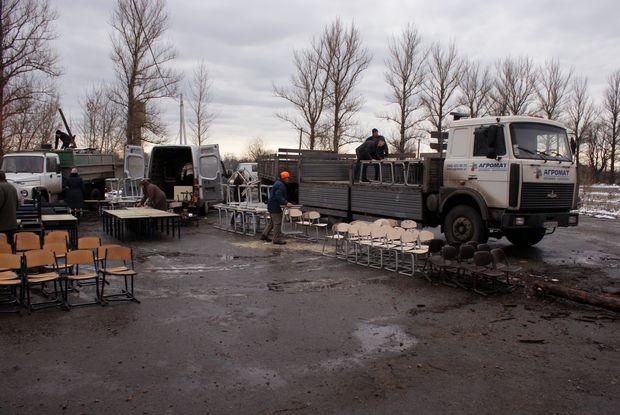 Вантажівка з причепом завантажує шкільні меблі