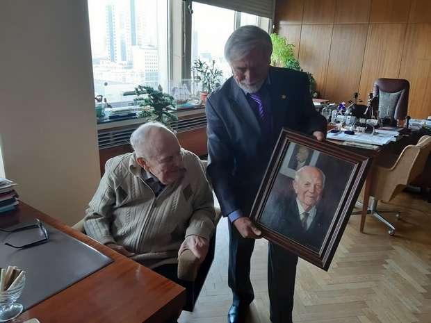 Заслужений художник Віктор Дем'янчук вручає картину Борису Патону